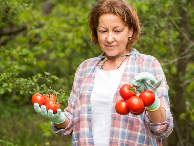 Elder woman holding a bunch of tomatoes