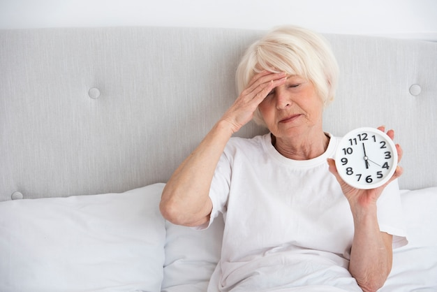 Elder woman holding a clock in her bed