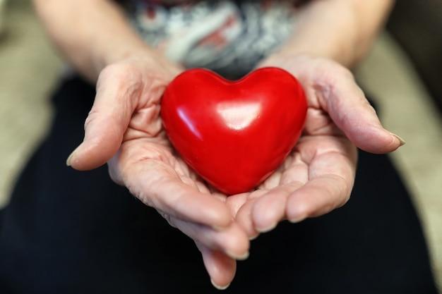 Пожилая женщина держит сердце