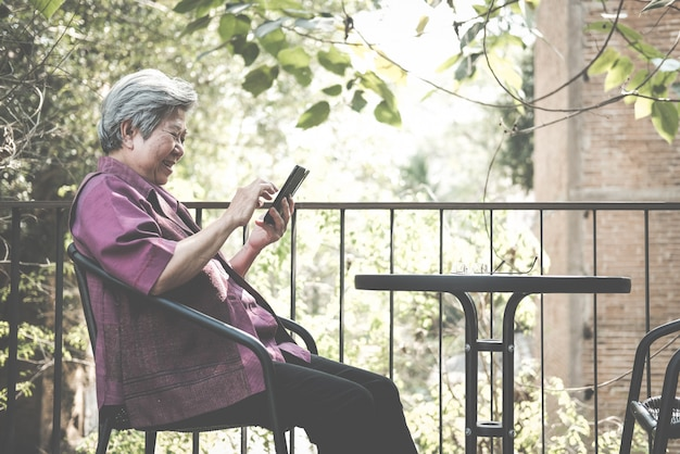 Elder woman holding mobile phone on terrace.