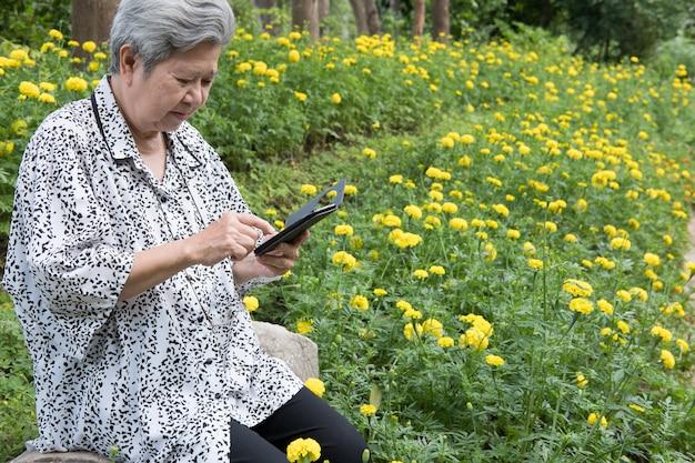 庭のベンチに座って携帯電話を保持している年配の女性。