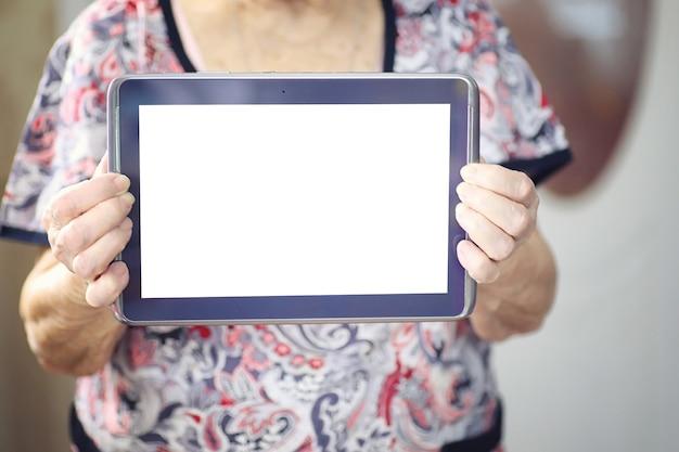 Пожилая женщина держит планшет