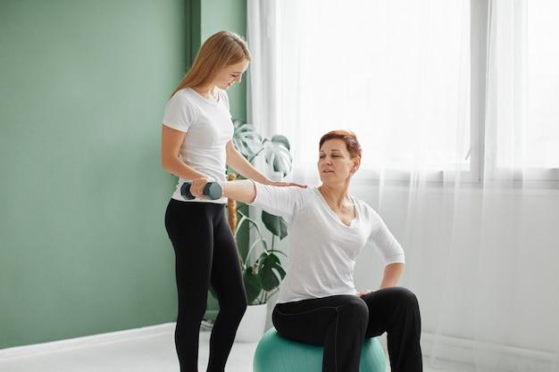 덤벨과 간호사와 함께 신체 운동을하는 covid 회복의 노인 여성