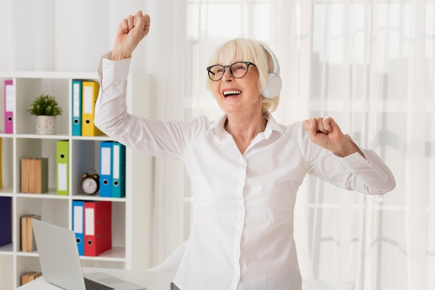Elder woman listening music in her office