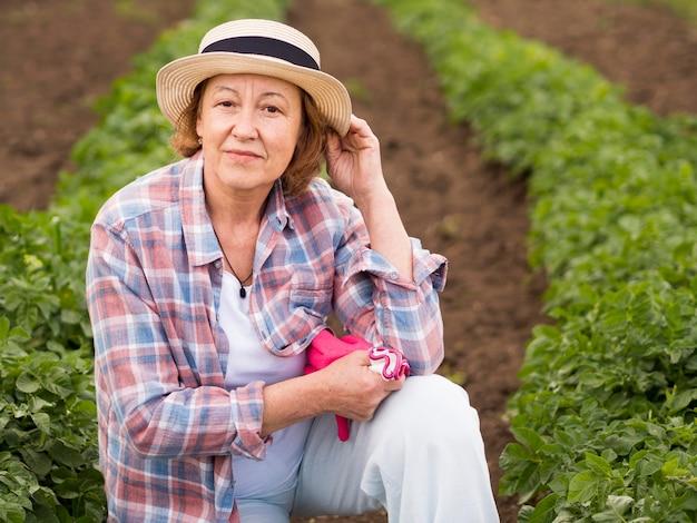 Старшая женщина позирует рядом с растением в своем саду