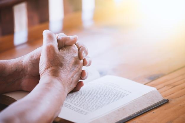 高齢の女性は聖書で祈る