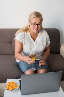 Elder woman in quarantine having a drink with laptop