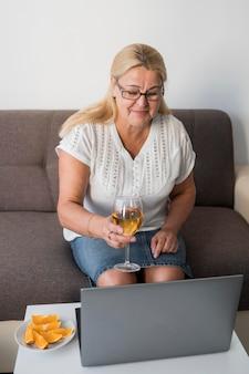 Donna anziana in quarantena bevendo un drink con il computer portatile