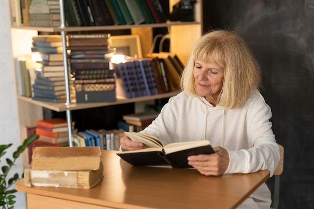 Пожилая женщина читает книгу дома