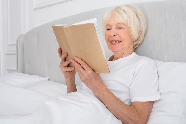 Elder woman reading a book in the bedroom