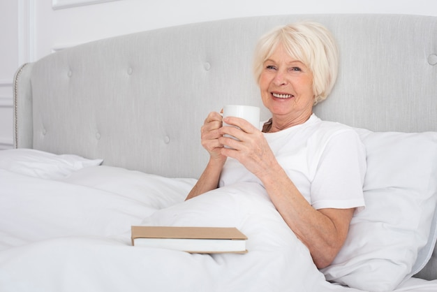 Elder woman reading a cup in the bedroom