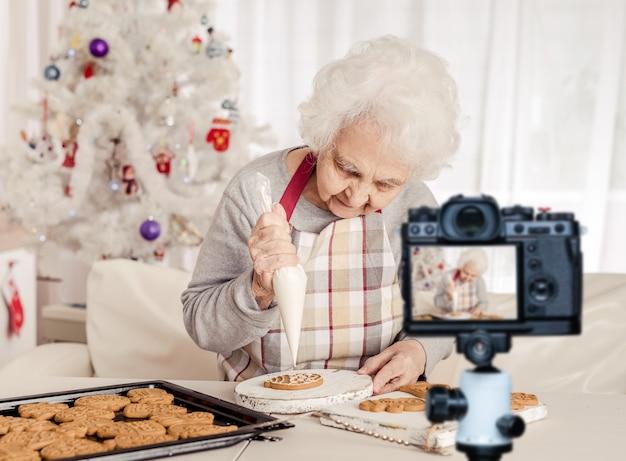 크리스마스 구운 쿠키에 크림을 몸을 담근 노인 여성