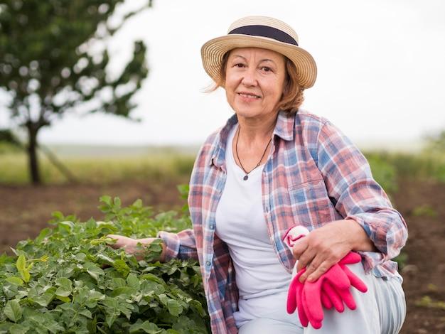 Пожилая женщина рядом с растением