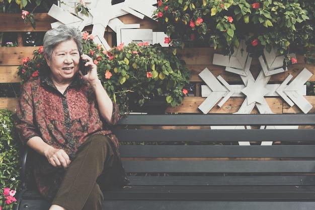 年配の女性は庭で携帯電話で話します。