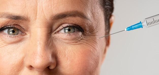 Пожилая женщина с помощью инъекций от морщин вокруг глаз