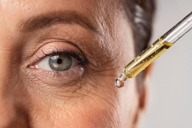 Пожилая женщина использует сыворотку от морщин вокруг глаз