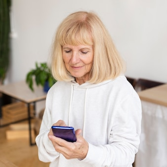 自宅でスマートフォンを使用している年配の女性