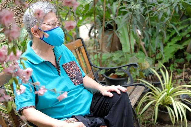 정원에서 쉬고 페이셜 마스크를 쓰고 노인 여성. 아시아 노인 여성 야외에서 휴식. 노인 레저 라이프 스타일