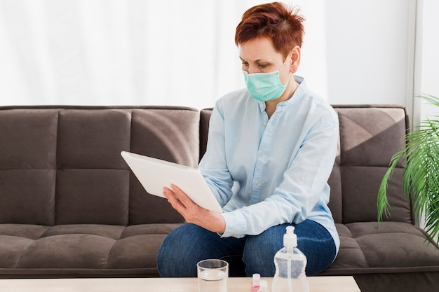 Elder woman wearing medical mask while holding tablet