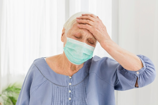 Elder woman with medical mask feeling unwell