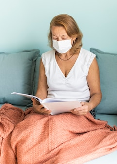 Elder woman with medical mask at home during the pandemic reading a book