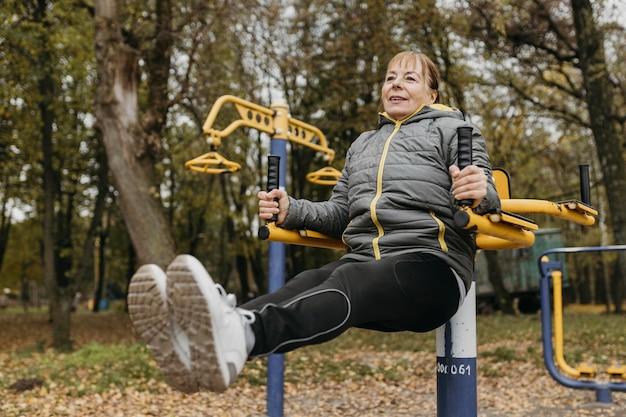 屋外で機器を使って運動する年配の女性