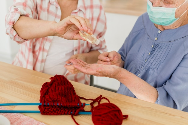 自宅で手を消毒する高齢女性