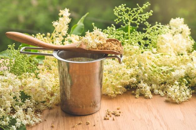 金属製のカップとニワトコの花のアレンジメント