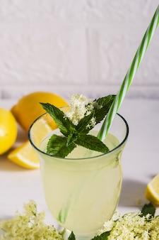 Бузина лимонад здоровый и освежающий летний напиток. закройте вверх домодельного сиропа elderflower в бутылке с elderflowers. летний напиток hugo champagne, напиток с сиропом из бузины, мятой и лаймом.