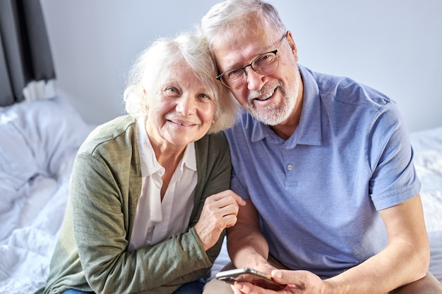 Elderly 60s husband and wife sit with smartphone relax on bed hugging,happy mature old couple rest in bedroom embrace look at camera show love and care