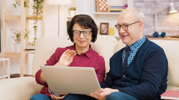 Elderly age couple sitting on sofa holding laptop during a video call. couple waving at laptop.