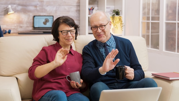 Elderly age couple wave at laptop during a video call with their family.