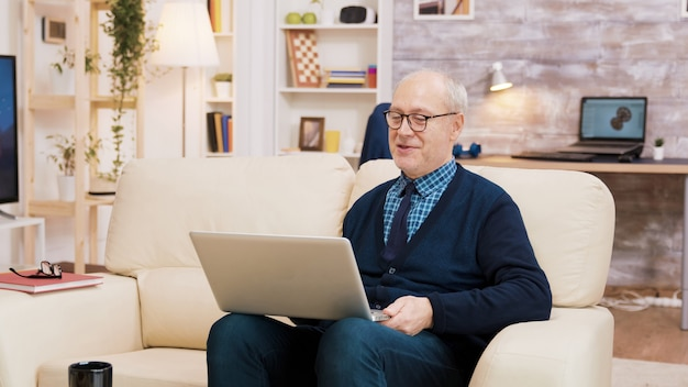 Elderly age couple with glasses sitting on sofa during a video call on laptop. aged couple using modern technology