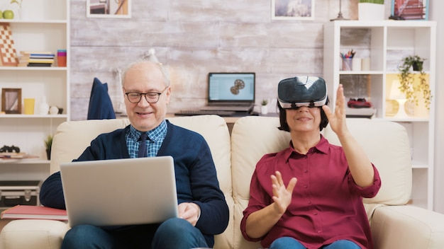 Elderly age woman sitting on sofa wearing virtual reality goggles. old man sitting on sofa using laptop next to his wife