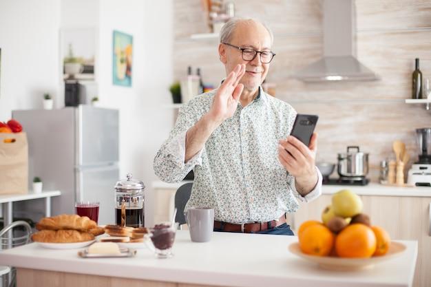 キッチンで家族とのビデオ会議中に手を振っている老人。インターネットオンラインチャット技術ビデオウェブカメラを使用してビデオ通話接続カメラ通信会議を行う高齢者