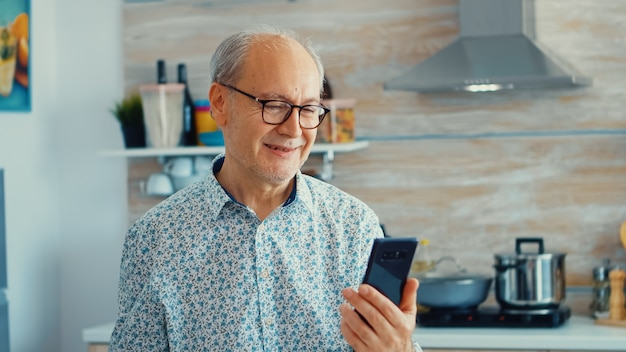 Elderly aged man waving during a video conference with family in kitchen. elderly person using internet online chat technology video webcam making a video call connection camera communication conferen