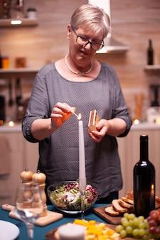 おいしい料理と一緒にキッチンでロマンチックなディナーの準備をしている高齢者。夫がロマンチックな夕食を待っている年配の女性。結婚記念日のお祝いの食事を準備する成熟した妻。