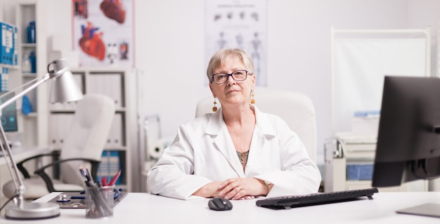 白衣を着た病院のキャビネットの高齢の女性医師。