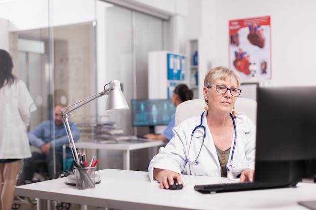 病院のオフィスでpcに取り組んでいる年配の女性医師、車椅子の無効な患者と話し合っている若いセラピストとコンピューター画面でx線を見ている看護師。