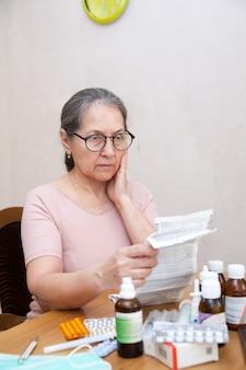自宅のテーブルで薬の注釈を読んでいる高齢者の驚いた女性