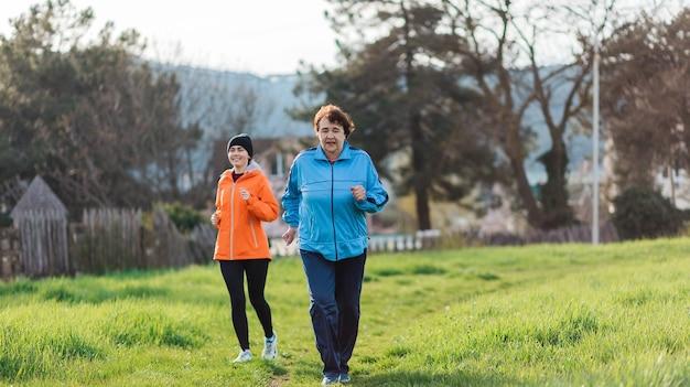 Пожилые и молодые улыбающиеся женщины в спортивной одежде бегут в парке. бабушка и внучка бегут вместе. международный день пожилых людей. концепция здорового образа жизни и спорта.