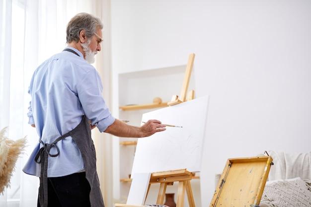 絵画に専念する年配の芸術家の男性、エプロンの白人男性は芸術の創造に没頭しています
