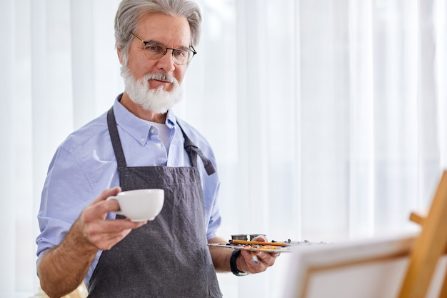 Elderly artist man drink tea during work in studio, gray-haired male in apron enjoys the process of drawing