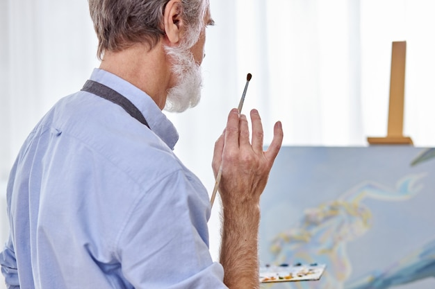 Elderly artist man holding paintbrush in hands and looking at his masterpiece on canvas