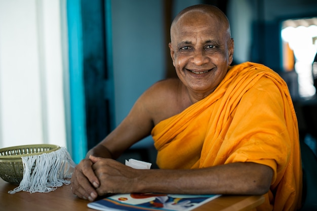 Elderly asian buddhist monk smiling at camera in buddhist monastery at river