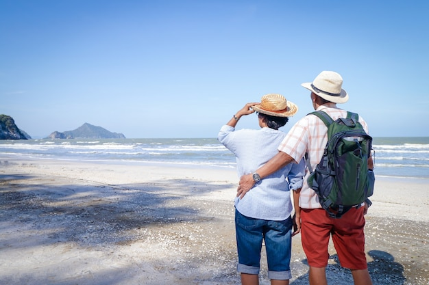An elderly asian couple hugging each other on the beach