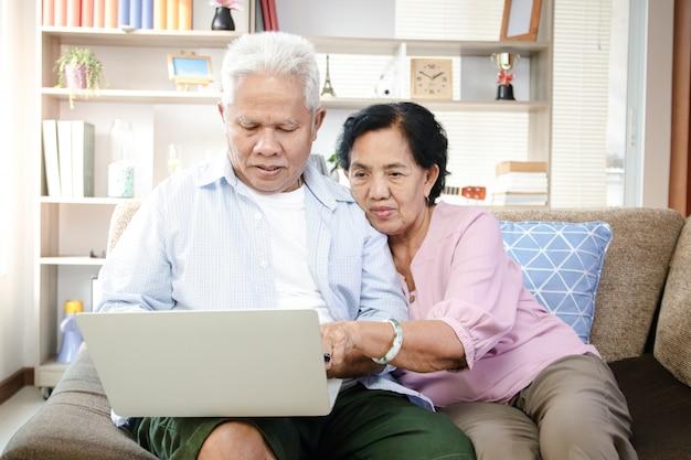 ソファーに座ってラップトップを使用して高齢者のアジアカップル