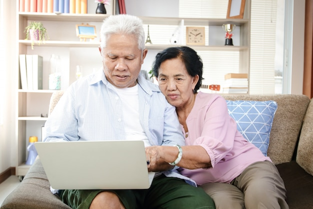 Elderly asian couple sitting on sofa and using laptop