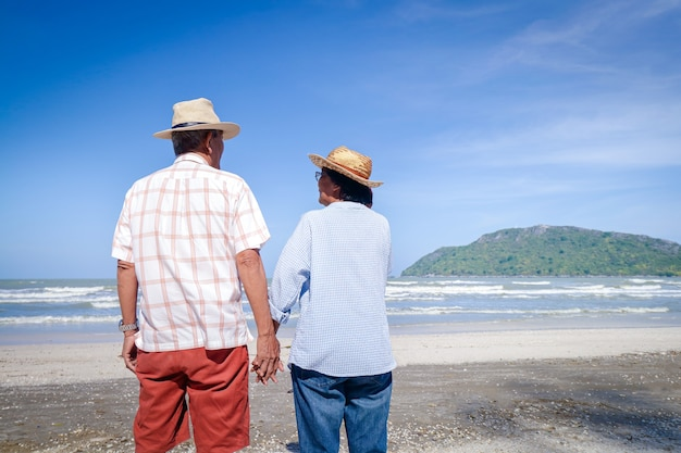 An elderly asian couple stand hand in hand on the beach look at the beautiful sea in the morning together. travel concept to live happily in retirement age. copy space