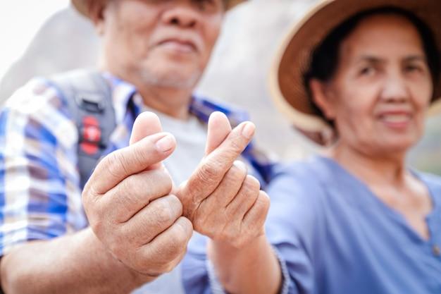 山でトレッキングし、退職後の生活を楽しむアジアの老夫婦